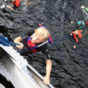 En konsentrert gutt klatrende i tau 10 meter over bakken